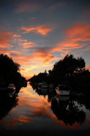 eventide: Reflection of Silhouette Treescape and Pleasure Boats Moored on Water Canal at Sunset