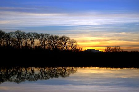Colorful Winter Sunset and Silhouette of Riparian Oak Trees Reflected in Wildlife Pond, San Jaoquin Delta, Central Valley, California