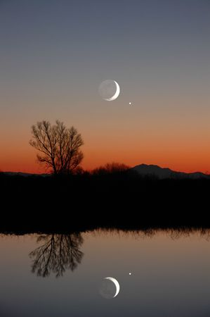 crescent: Stylized Winter Moon, Venus, and Silhouette of Lone Winter Willow Tree, in Pefect Natural Reflected on Quiet Slough, Evening, Central Valley, California Stock Photo