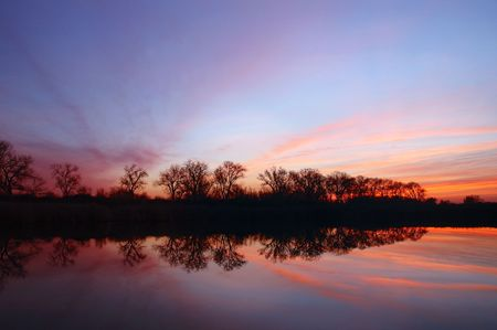 eventide: Tiger Claw Clouds and Riparian Winter Oak Tree Reflection Silhouetted against Sunset