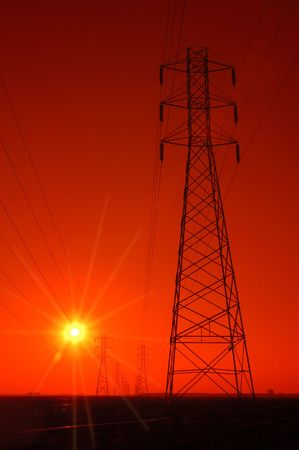 Electrical Tower and Powerlines at Dark Red Sunset