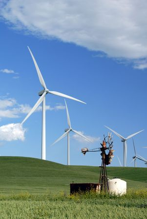 Stark White Electrical Power Generating Wind Turbines on Rolling Wheat Covered Hills, Contrasted by Old Ranch Water Pumping Windmill, Rio Vista, California photo