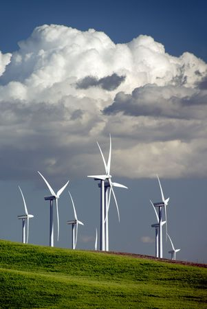 Stark White Electrical Power Generating Windmills on Rolling Hills of Spring Green Wheat, Beneath Spring Clouds, Rio Vista, California Stock Photo