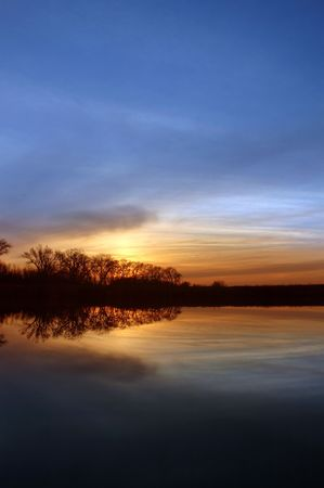 california delta: Colorful Winter Sunset and Silhouette of Riparian Oak Trees Reflected in Wildlife Pond, San Jaoquin Delta, Central Valley, California
