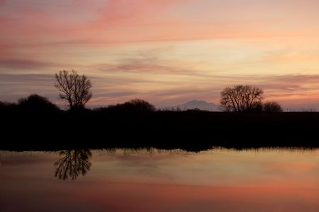 eventide: Silhouette of Riparian Pond Under Pink Sky Just After Sundown, Wildlife Area, Central Valley, California Stock Photo