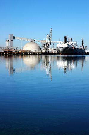 Cargo Ship Reflected near Seaport Loading Docks at Sunset, California, USA