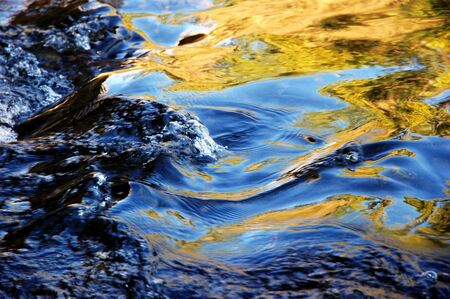 contrasty: Contrasty Reflection of Autumn Trees and Blue Sky Splashing in Running Mountain Stream Water
