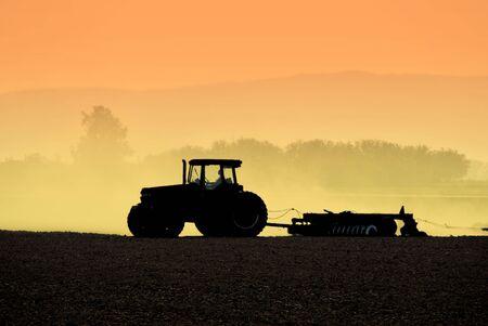 ploegen: Gedempt Backlit Silhouette of Two Tractoren strijkvuur Bodem Stockfoto