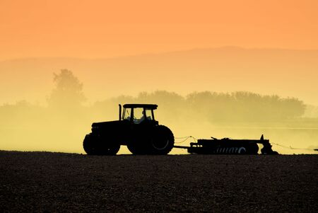Muted Backlit Silhouette of Two Tractors Raking Soil