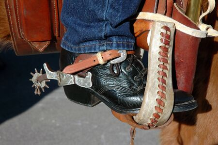 spurs: Western Lacer Boot With Spurs Resting In Stirrup