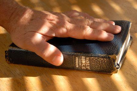 塗られたライトの下でよく使用される古い聖書に手します。 写真素材