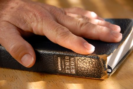 Hand On Well Used Old Bible Under Painted Light Standard-Bild