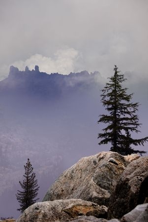 ridgeline: Rugged ridgeline obscured by clouds, framed by trees and granite.