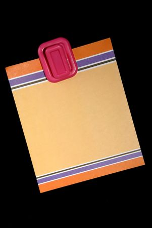 Blank colored note paper hanging from magnetic pinup on black background.. Stock Photo - 2423002
