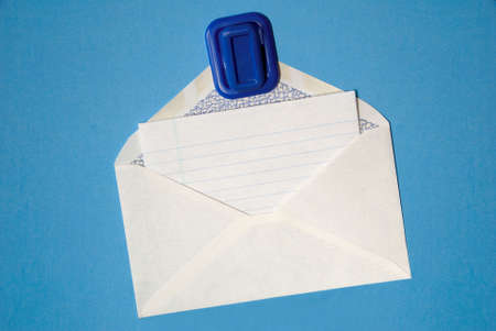 Blank white note paper in white envelope hanging from magnetic pinup on blue background.. Stock Photo - 2423030
