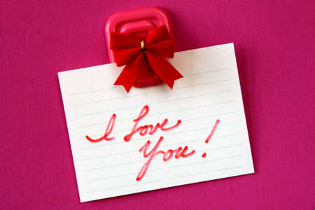 Red I love you note hanging from magnetic pinup on magenta background.. Stock Photo - 2423028