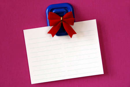 Blank white note paper hanging from magnetic pinup with red bow on pink background.. Stock Photo - 2423025