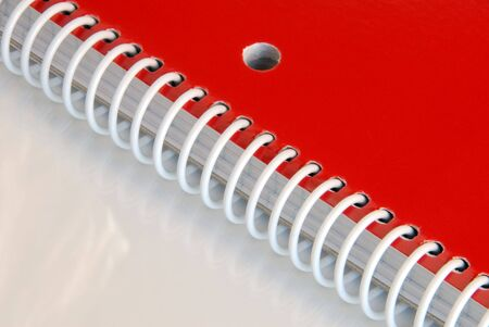 Close up of red spiral notebook on reflective surface. Stock Photo - 2423001