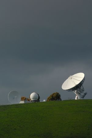 White Satellite Communications Antenna Dishes Against Stormy Setting