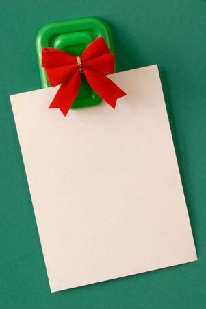 緑の背景に磁気ピンナップから掛かっている白い空白のメモ用紙. 写真素材