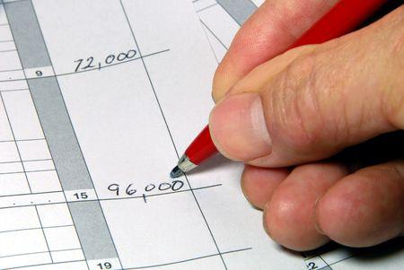 capital gains: Closeup of Hand Writing Numerical Figures Stock Photo