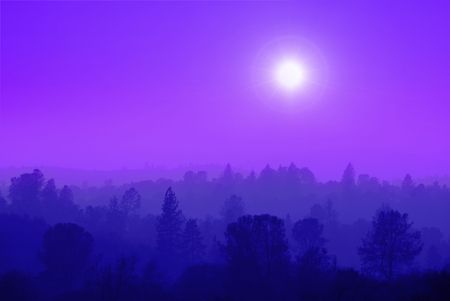 against the sun: Foothill ranges in muted purple mist against setting sun. Stock Photo