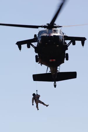 軍のヘリコプター救助操作のシルエット。