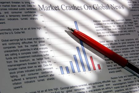 Selective focus closeup of fictitious news and graph indicating financial market downward movement with red pen, under dramatic lighting. (Photographer holds copyright for represented text and copy) Stock Photo