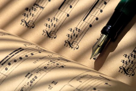 Detail of 100 year old grungy sheet music with vintage fountain pen.