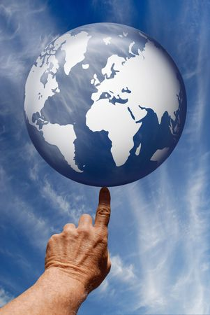 Synthetic digital blue globe poised on a single finger tip against a summer sky with cirrus clouds.