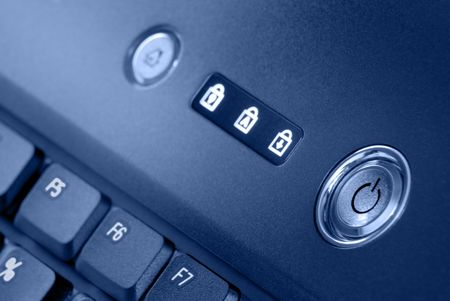 Detail of laptop power switch, indicator lights, and keyboard against grainy surface  in popular muted blue tones.  photo