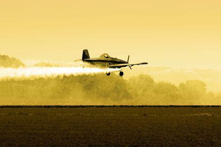 フィールドに午後遅く低を飛んで作物ダスター 写真素材