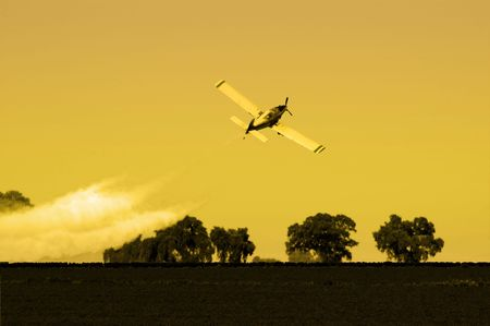 pesticides: Crop Duster Flying Low over Fields In Late Afternoon
