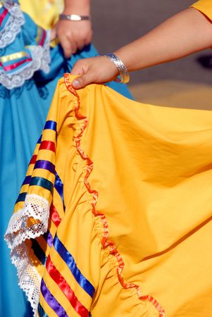 オレンジ色の民族のメキシコのドレスを持っている若い女の子の手