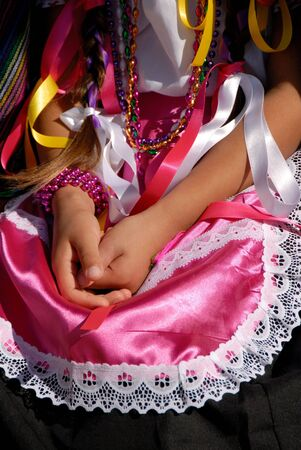 Young Girls Hands Folden in Her Lap on Pink Ethnic Mexican Dress photo