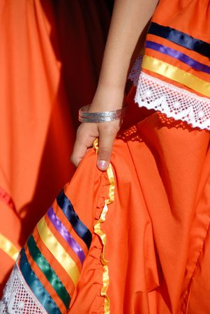traje mexicano: Young Girl's Hand Holding Out naranja étnico mexicano de vestir  Foto de archivo
