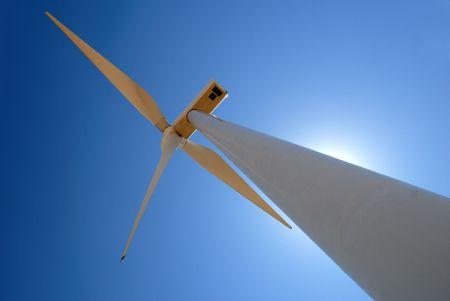 against the sun: Power generating wind turbine against sun and blue sky, Rio Vista California. Stock Photo