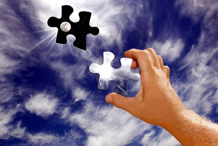Hand Holding Sun and Moon Puzzle Piece Leaving Hole in the Sky Stock Photo