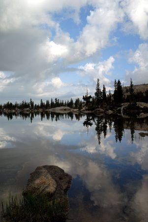 emigrant: Sierra Nevada trees, dramatic clouds, and granite dome reflected in wilderness lake (Wire Lake, twelve mile backpack into Emigrant Wilderness)