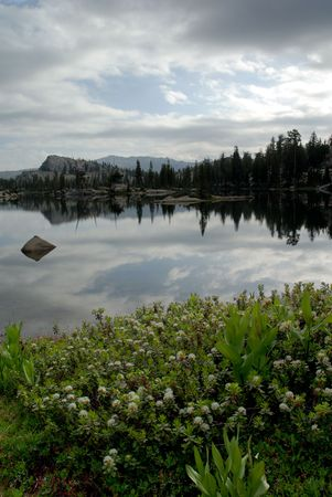emigrant: Overcast mood of Sierra Nevada trees, dramatic clouds, and granite dome reflected in wilderness lake (Wire Lake, twelve mile backpack into Emigrant Wilderness)