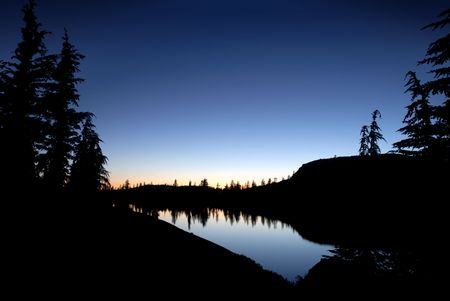 Silhouette of Sierra Nevada trees and granite dome reflected in wilderness lake (Wire Lake, twelve mile backpack into Emigrant Wilderness) Banco de Imagens