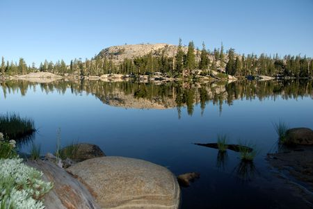 emigrant: Sierra Nevada trees and granite dome reflected at dawn in wilderness lake (Wire Lake, twelve mile backpack into Emigrant Wilderness)