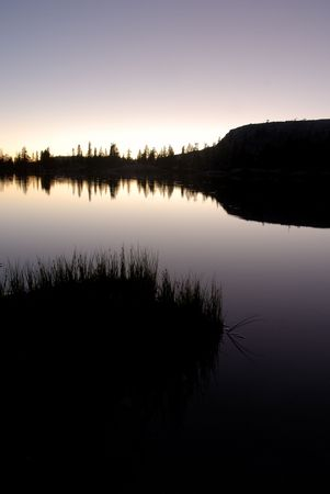 Silhouette of Sierra Nevada trees and granite dome reflected in wilderness lake (Wire Lake, twelve mile backpack into Emigrant Wilderness) Stock Photo - 3420841
