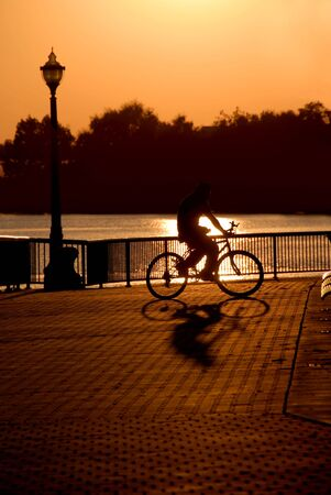 weber: Extreme silhouette of casual cyclist in public park, Weber Point, Stockton California Stock Photo