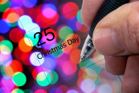 Three dimensional Christmas Day calendar, December 25, with pen in hand taking note, and defocused Christmas lights Banco de Imagens
