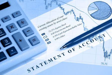 Asset statement, declining graph line, calculator, and pen
