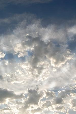 青い夜の夏の空に明るい雲の層の上の太陽の光線