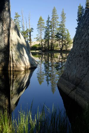 Trees and Granite Reflected in Small California Sierra Nevada Wilderness Lake