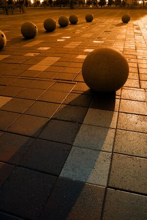 Extreme silhouette of granite spheres in public park with wet pavement at Weber Point in Stockton California Stock Photo