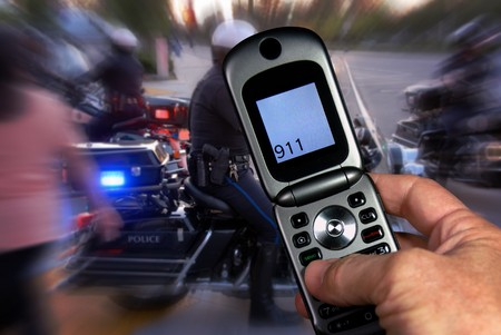 Dialing 911 on the cell phone at emergency scene, excitement indicated with motion blur